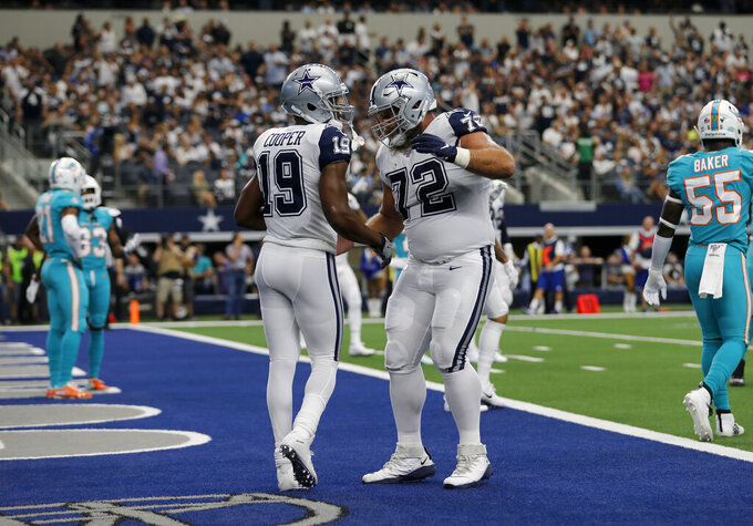 Dallas Cowboys' Amari Cooper (19) and Travis Frederick (72) celebrate a touchdown catch by Cooper as Miami Dolphins' Jerome Baker walks away in the first half of a NFL football game in Arlington, Texas, Sunday, Sept. 22, 2019. (AP Photo/Michael Ainsworth)