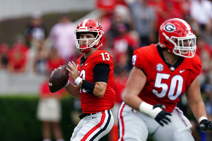 Georgia quarterback Stetson Bennett (13) throws behind offensive lineman Warren Ericson (50) during the first half of an NCAA college football game against UAB, Saturday, Sept. 11, 2021, in Athens, Ga. (AP Photo/John Bazemore)