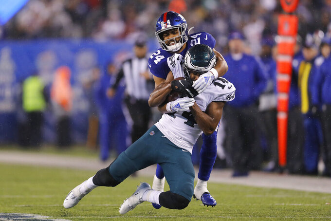 Philadelphia Eagles wide receiver Robert Davis (14) is stopped by New York Giants cornerback Julian Love (24) after catching a pass in the second half of an NFL football game, Sunday, Dec. 29, 2019, in East Rutherford, N.J. (AP Photo/Adam Hunger)