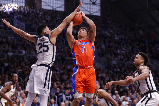 Butler forward Christian David (25) blocks the shot of Florida forward Keyontae Johnson (11) in the second half of an NCAA college basketball game in Indianapolis, Saturday, Dec. 7, 2019. Butler defeated Florida 76-62. (AP Photo/Michael Conroy)