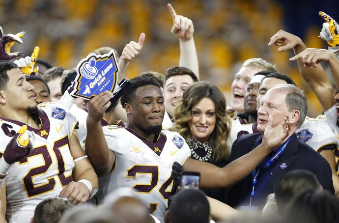 FILE - In this Dec. 26, 2018, file photo, Minnesota running back Mohamed Ibrahim (24) acknowledges teammates and fans after receiving the MVP trophy after Quick Lane Bowl NCAA college football game against Georgia Tech, in Detroit. Minnesota returns a major portion of its offense from the strong finish to last season that featured a dominant victory at rival Wisconsin, led by wide receiver Tyler Johnson and running back Mohamed Ibrahim. (AP Photo/Carlos Osorio, File)
