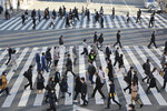People wearing face masks to protect against the spread of the coronavirus cross an intersection on a street in Tokyo, Wednesday, Jan. 13, 2021. Japan expanded a coronavirus state of emergency for several more prefectures, affecting more than half the population as infections spread across the country. (AP Photo/Koji Sasahara)