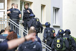 Officers of the federal police go into an apartment building as part of a search in Weissenfles, Germany, Wednesday, Sept. 23, 2020. The federal police searched more than 60 residential and business premises in five states on Wednesday on suspicion of illegal smuggling of workers for the meat industry. Approximately 800 officers were involved in the raid - mainly in Saxony-Anhalt and Lower Saxony, according to a spokesperson for the Central German Federal Police. The nationwide raid on the illegal smuggling of workers for the meat industry will focus on Weissenfels. (Jan Woitas/dpa via AP)