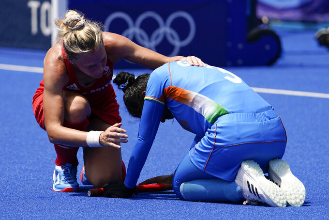 Britain's Leah Julia Wilkinson, left, comforts India's Deep Grace Ekka after Britain won their women's field hockey bronze medal match at the 2020 Summer Olympics, Friday, Aug. 6, 2021, in Tokyo, Japan. Britain won 4-3. (AP Photo/John Locher)