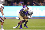 Washington's Giles Jackson, left, is brought down by Montana's Omar Hicks Onu in the second half of an NCAA college football game Saturday, Sept. 4, 2021, in Seattle. Montana won 13-7. (AP Photo/Elaine Thompson)