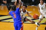 Vanderbilt guard Tyrin Lawrence looks to pass the ball as Florida forward Omar Payne (5) defends during the first half of an NCAA college basketball game Wednesday, Dec. 30, 2020, in Nashville, Tenn. (AP Photo/John Amis)