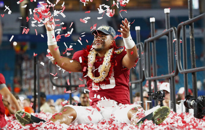 FILE - In this Dec. 30, 2018, file photo, Alabama quarterback Tua Tagovailoa throws confetti in the air after winning the Orange Bowl NCAA college football game against Oklahoma, in Miami Gardens, Fla. Tagovailoa had to settle for second place in the Heisman Trophy balloting, but he delivered arguably the best bowl performance of any player in the country. Tagovailoa outdueled Heisman Trophy winner Kyler Murray of Oklahoma in the Sugar Bowl to earn his spot as the quarterback of our all-bowl team. (AP Photo/Wilfredo Lee, File)