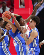 Memphis guard Boogie Ellis, left, gets the rebound behind Houston center Brison Gresham, middle, as Memphis guard Lester Quinones, right, looks on during the first half of an NCAA college basketball game Sunday, March 8, 2020, in Houston. (AP Photo/Michael Wyke)