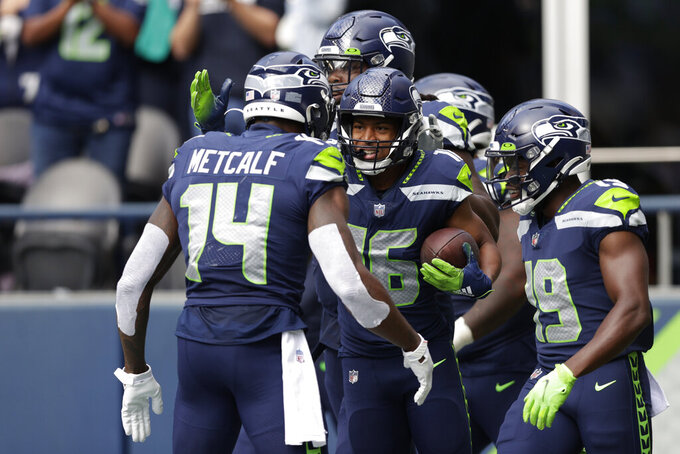 Seattle Seahawks wide receiver Tyler Lockett (16) is greeted by wide receivers DK Metcalf (14) and Penny Hart (19) after Lockett caught a pass for a touchdown against the Tennessee Titans during the first half of an NFL football game, Sunday, Sept. 19, 2021, in Seattle. (AP Photo/John Froschauer)