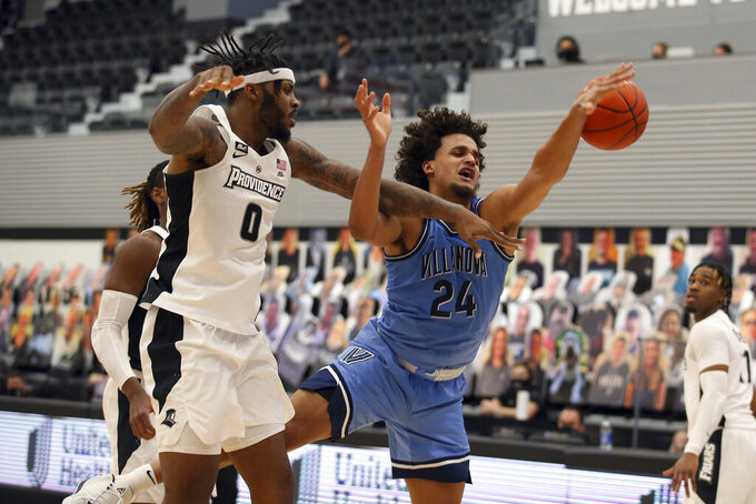 Providence's Nate Watson (0) and Villanova's Jeremiah Robinson-Earl (24) battle for a rebound during an NCAA college basketball game in Providence, R.I., Saturday, March 6, 2021. (AP Photo/Stew Milne)