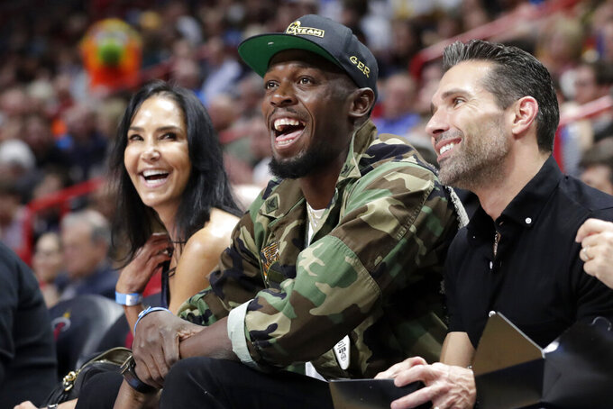 FILE - In this Dec. 13, 2019, file photo, Usain Bolt watches the first half of an NBA basketball game between the Miami Heat and Los Angeles Lakers in Miami. The retired world's fastest man is not only changing diapers these days, but also distances as he makes a brief comeback for a promotional event.(AP Photo/Lynne Sladky, File)