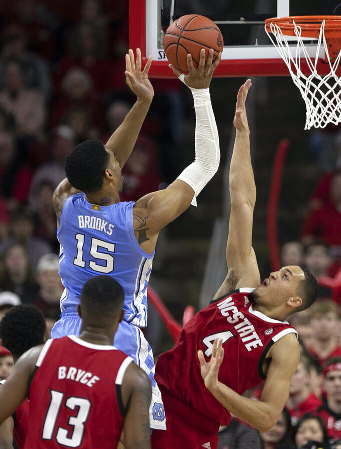 North Carolina's Garrison Brooks (15) puts up a shot against North Carolina State's Jericole Hellems (4) during the first half of an NCAA college basketball game at PNC Arena in Raleigh, N.C., Monday, Jan. 27, 2020. (Robert Willett/The News & Observer via AP)