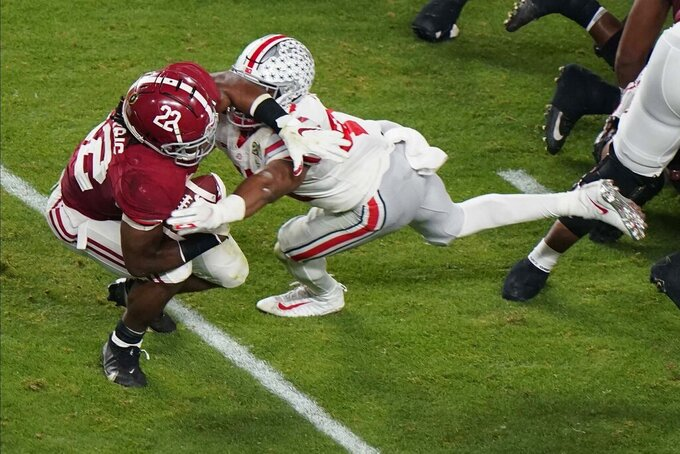 Alabama running back Najee Harris is tackled by Ohio State linebacker Justin Hilliard during the first half of an NCAA College Football Playoff national championship game, Monday, Jan. 11, 2021, in Miami Gardens, Fla. (AP Photo/Wilfredo Lee)
