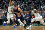 Dallas Mavericks guard Luka Doncic, center, drives between Boston Celtics forward Jayson Tatum (0) and guard Brad Wanamaker, right, during the second half of an NBA basketball game in Boston, Monday, Nov. 11, 2019. The Celtics defeated the Mavericks 116-106. (AP Photo/Charles Krupa)