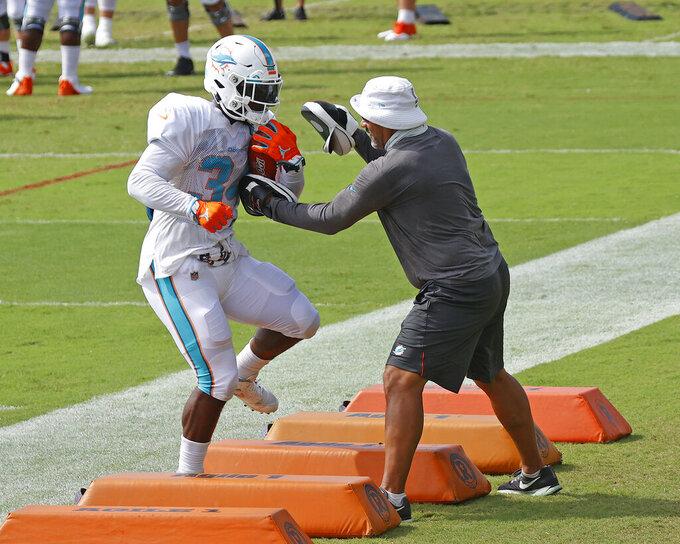 Miami Dolphins running back Jordan Howard (34) runs a drill during an NFL football training camp practice in Davie, Fla., Monday, Aug. 17, 2020. (AP Photo/Joel Auerbach)