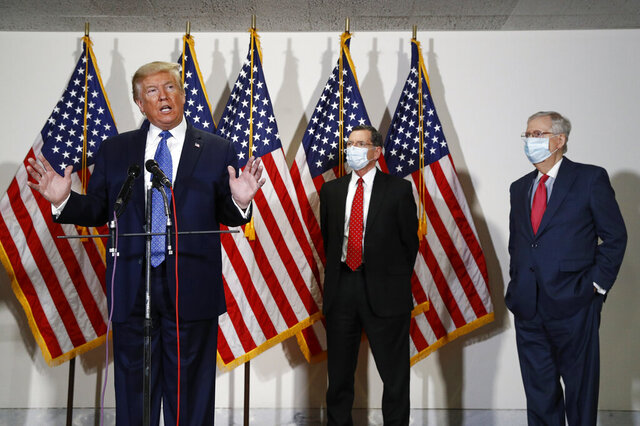 President Donald Trump speaks with reporters after meeting with Senate Republicans at their weekly luncheon on Capitol Hill in Washington, Tuesday, May 19, 2020. Standing behind Trump are Sen. John Barrasso, R-Wyo., second from right, and Senate Majority Leader Mitch McConnell of Ky. (AP Photo/Patrick Semansky)