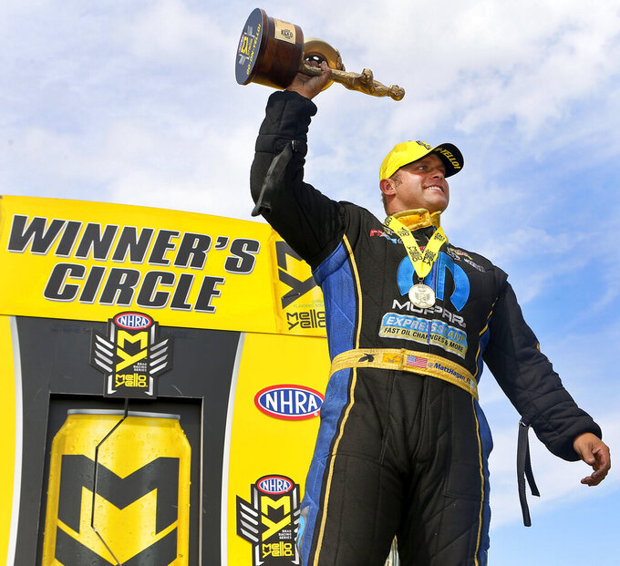 FILE - In this May 22, 2016, file photo, funny Car driver Matt Hagan lifts his trophy into the air after winning the NHRA Kansas Nationals in Topeka, Kan. Don Schumacher Racing has won the last 14 events in the NHRA's Funny Car division. It's a record for the racing series (Chris Neal/The Topeka Capital-Journal via AP, File)
