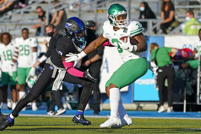 North Texas running back DeAndre Torrey, right, spins away from Middle Tennessee safety Gregory Grate Jr., left, in the first half of an NCAA college football game Saturday, Oct. 17, 2020, in Murfreesboro, Tenn. (AP Photo/Mark Humphrey)
