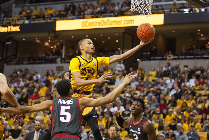 Missouri's Xavier Pinson, top, shoots over Arkansas' Jalen Harris, bottom left, and Adrio Bailey, right, during the second half of an NCAA college basketball game Saturday, Feb. 8, 2020, in Columbia, Mo. Missouri beat Arkansas 83-79 in overtime. (AP Photo/L.G. Patterson)