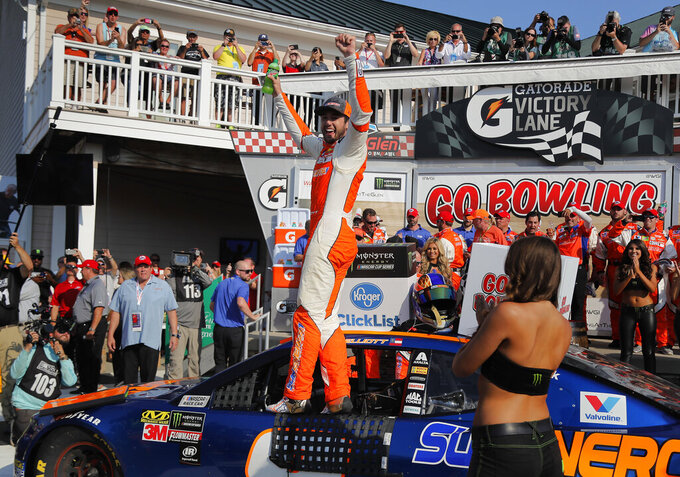 "FILE - In this Aug. 5, 2018, file photo, Chase Elliott, center, celebrates after winning a NASCAR Cup Series auto race in Watkins Glen, N.Y. Three months after its opening day was canceled by the coronavirus pandemic, Watkins Glen International is hosting car clubs again as NASCAR weekend looms in mid-August. ""Everybody is excited about getting back in the saddle. I know we are,"" track president Michael Printup said. (AP Photo/Julie Jacobson, File)"