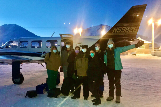 In this undated photo, provided by the Tanana Chiefs Conference, shows a team from the tribal health organization posing outside a plane before leaving for a rural vaccination clinic in Anaktuvuk Pass, Alaska. Some of Alaska's highest vaccination rates among those 16 or older have been in some of its remotest, hardest-to-access communities, where the toll of past flu or tuberculosis outbreaks hasn't been forgotten. (Tanana Chiefs Conference via AP)