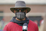 Reporters standing socially distanced from Washington State head coach Nick Rolovich are reflected in Rolovich's sunglasses as he talks after the first day of NCAA college football practice, Friday, Aug. 6, 2021, in Pullman, Wash. Rolovich would like for attention going into the 2021 season to be focused on players on the field, but he is getting just as much attention around his decision not to receive a COVID-19 vaccination.(AP Photo/Ted S. Warren)