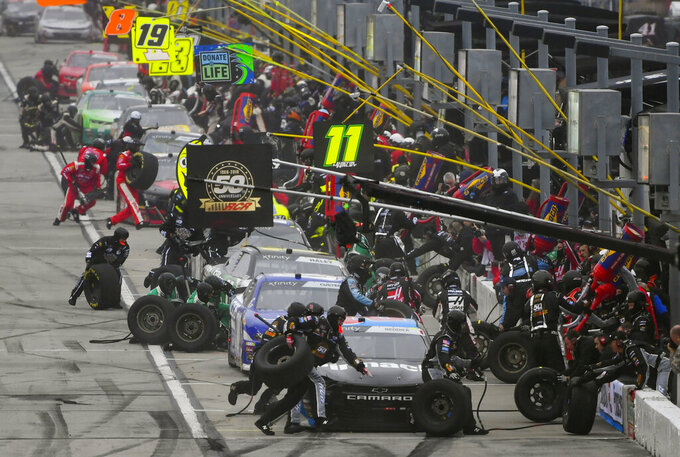 Crew members tend to Tyler Reddick's car in front as others pits stop along with him during a NASCAR Xfinity auto race at Atlanta Motor Speedway, Saturday, Feb. 23, 2019, in Hampton, Ga. (AP Photo/John Amis)