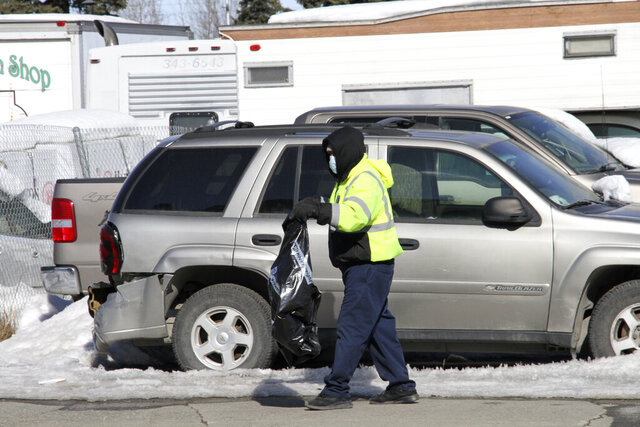 A man wearing a mask picks up trash on a street Monday, March 30, 2020, in Anchorage, Alaska. A third Alaskan has died from COVID-19. State health officials say a 73-year-old Anchorage resident was the latest fatality. The individual was tested and admitted to an Anchorage hospital March 23 and died Saturday. (AP Photo/Mark Thiessen)
