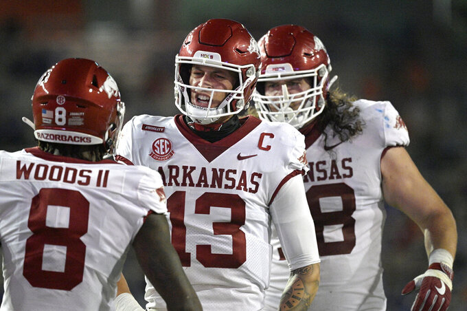 Arkansas quarterback Feleipe Franks (13) reacts after throwing for a 47-yard touchdown to wide receiver Mike Woods (8) during the first half of the team's NCAA college football game against Florida, Saturday, Nov. 14, 2020, in Gainesville, Fla. (AP Photo/Phelan M. Ebenhack)