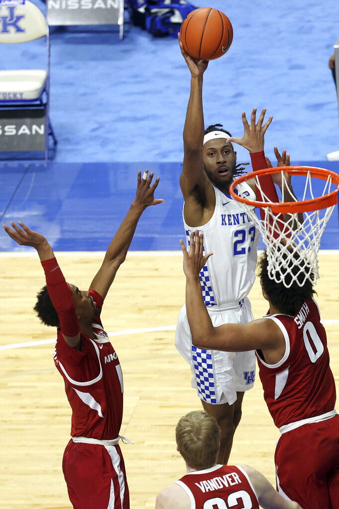 Kentucky's Isaiah Jackson, middle, shoots while defended by Arkansas' Jalen Tate, left, and Justin Smith (0) during the second half of an NCAA college basketball game in Lexington, Ky., Tuesday, Feb. 9, 2021. (AP Photo/James Crisp)