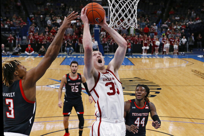 FILE - In this Tuesday, Feb. 25, 2020 ,file photo, Oklahoma forward Brady Manek (35) shoots between Texas Tech guard Jahmi'us Ramsey (3) and guard Chris Clarke (44) in the second half of an NCAA college basketball game in Oklahoma City. The Sooners won three of their last four games last season to finish in a tie for third place in the Big 12. Plenty of talent returns, led by seniors Austin Reaves and Brady Manek. (AP Photo/Sue Ogrocki, File)