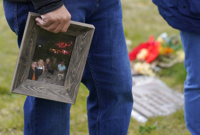 Joe Woodmansee holds a photo of the last time he and his three siblings were together with their mother, Carole Rae Woodmansee, as he visits Carole's grave, Saturday, March 27, 2021, at Union Cemetery in Sedro-Woolley, Wash., north of Seattle, prior to a memorial service. Carole died a year ago on the same date in 2020 — the day of her 81st birthday — from complications of COVID-19 after contracting it during a choir practice that sickened 53 people and killed two — a superspreader event that would become one of the most pivotal transmission episodes in understanding the virus. (AP Photo/Ted S. Warren)
