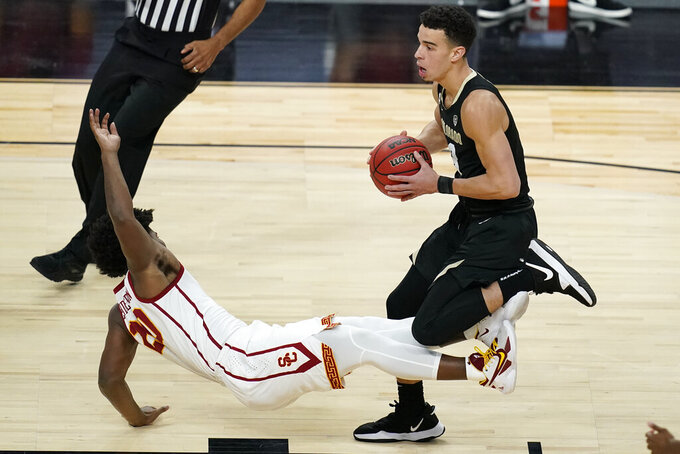 Colorado's Maddox Daniels, right, fouls Southern California's Ethan Anderson during the first half of an NCAA college basketball game in the semifinal round of the Pac-12 men's tournament Friday, March 12, 2021, in Las Vegas. (AP Photo/John Locher)