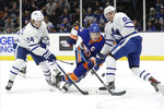 Toronto Maple Leafs' Cody Ceci (83) and Kasperi Kapanen (24) defend New York Islanders' Anders Lee (27) during the second period of an NHL hockey game Wednesday, Nov. 13, 2019, in Uniondale, N.Y. (AP Photo/Frank Franklin II)