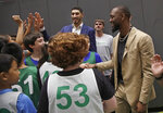 Newly acquired Boston Celtics guard Kemba Walker, right, and center Enes Kanter, background left, greet Celtics camp players at the team basketball practice facility, Wednesday, July 17, 2019, in Boston. (AP Photo/Elise Amendola)