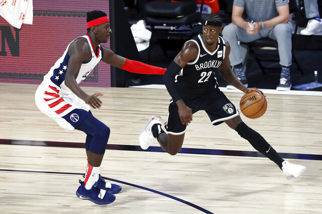 Brooklyn Nets guard Caris LeVert (22) dribbles against Washington Wizards forward Isaac Bonga (17) in the first half of an NBA basketball game Sunday, Aug. 2, 2020, in Lake Buena Vista, Fla. (Kim Klement/Pool Photo via AP)