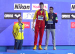 FILE - In this Sunday, July 21, 2019 file photo, China's Sun Yang, centre, holds up his gold medal as silver medalist Australia's Mack Horton, left, stands away from the podium with bronze medalist Italy's Gabriele Detti at right, after the men's 400m freestyle final at the World Swimming Championships in Gwangju, South Korea. One of China's biggest Olympic stars will undergo a rare public trial of a doping case on Friday, Nov. 15, 2019 with his 2020 Tokyo Games place at stake. Three-time gold medalist swimmer Sun Yang is facing a World Anti-Doping Agency appeal in Switzerland that seeks to ban him for up eight years.  (AP Photo/Mark Schiefelbein, File)