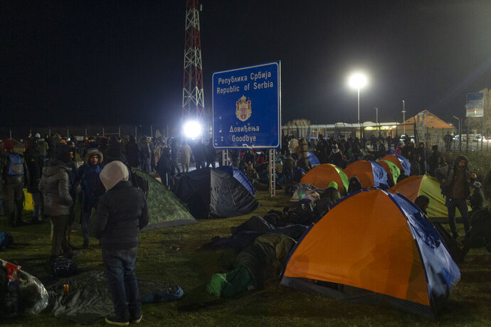 Migrants and refugees gather at a border crossing between Serbia and Hungary in Kelebija, Serbia, Thursday, Feb. 6, 2020. About two hundred migrants, including children, gathered Thursday at Serbia's border with Hungary to demand to be allowed entry into the European Union country. (AP Photo/Marko Drobnjakovic)