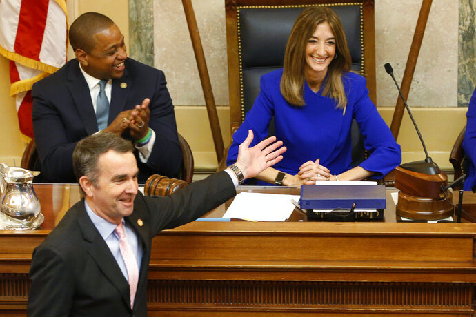 FILE - This Wednesday Jan. 8, 2020 file photo shows Virginia Gov. Ralph Northam, bottom left, as he recognizes House speaker, Eileen Filler-Corn, D-Farifax, right, while he prepares to deliver his State of the Commonwealth address as Lt. gov. Justin Fairfax, top left, applauds before a joint session of the Virginia Assembly at the Virginia state Capitol in Richmond, Va. (AP Photo/Steve Helber)