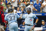 Toronto Blue Jays' Vladimir Guerrero Jr. (27) and Marcus Semien (10) celebrate after Guerrero Jr. hits a home run during the fifth inning of a baseball game against the Boston Red Sox, Sunday, Aug. 8, 2021 in Toronto. (Christopher Katsarov/The Canadian Press via AP)
