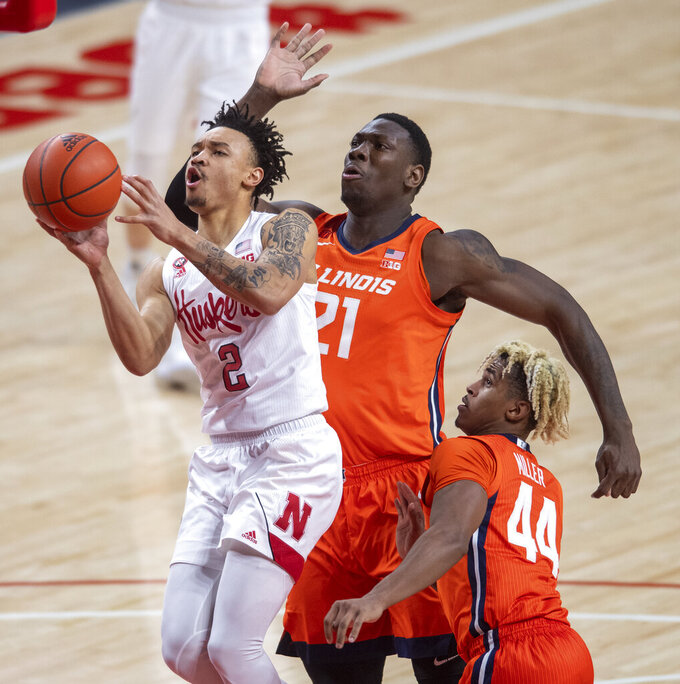 Nebraska guard Trey McGowens (2) drives to the basket against Illinois' Kofi Cockburn (21) and Adam Miller (44) during the first half of an NCAA college basketball game on Friday, Feb. 12, 2021, in Lincoln, Neb. (Francis Gardler/Lincoln Journal Star via AP)