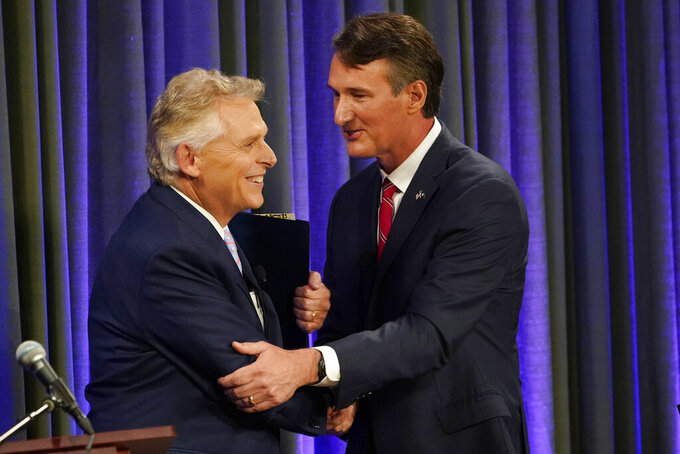 Democratic gubernatorial candidate and former governor Terry McAuliffe, left, greets his Republican challenger, Glenn Youngkin, after a debate at the Appalachian School of Law in Grundy, Va., Thursday, Sept. 16, 2021. (AP Photo/Steve Helber)