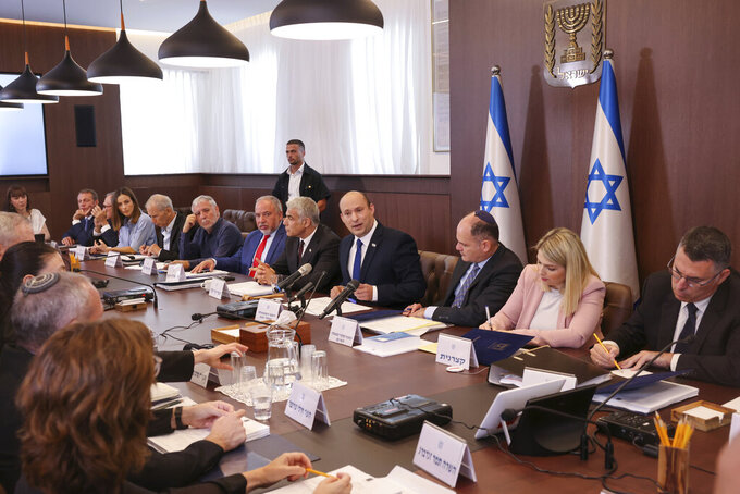 """Israeli Prime Minister Naftali Bennett, center, chairs the first weekly cabinet meeting of the new government in Jerusalem, Sunday, June 20, 2021. Bennett opened his first Cabinet meeting on Sunday since swearing in his new coalition government with a condemnation of the newly elected Iranian president, whom he called """"the hangman of Tehran."""" (Emmanuel Dunand/Pool Photo via AP)"""