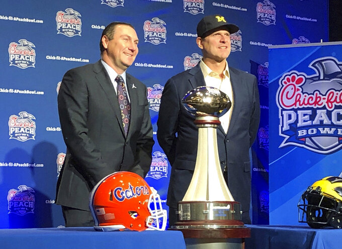 Florida Head Coach Dan Mullen, left, and Michigan Head Coach Jim Harbaugh stand alongside the George P. Crumbley Trophy, in Atlanta, GA., Friday, Dec. 28, 2018. The teams will play in the Peach Bowl Saturday. (AP Photo/ Charles Odum)