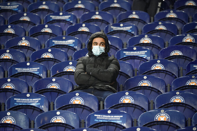 A fan wearing a face mask sits alone on the stands before the start of the Champions League group C soccer match between FC Porto and Olympiacos at the Dragao stadium in Porto, Portugal, Tuesday, Oct. 27, 2020. Only 3,750 fans were allowed on the stands. (Miguel Riopa, Pool via AP)