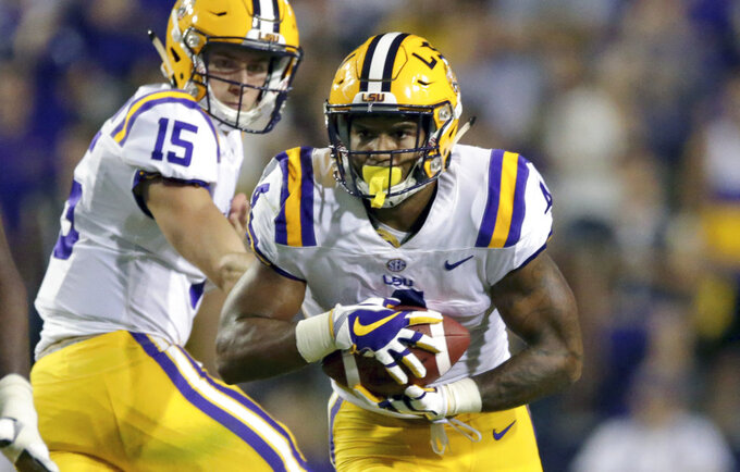 FILE - In this Sept. 9, 2017, file photo, LSU running back Nick Brossette carries the ball after a handoff from quarterback Myles Brennan (15) during the second half of an NCAA college football game in Baton Rouge, La. No. 25 LSU will learn a lot about its unproven running game right away. Nick Brossette and Clyde Edwards-Helaire are the top two in the running back rotation after playing sparingly behind Derrius Guice and Darrel Williams last season. (AP Photo/Rusty Costanza, File)