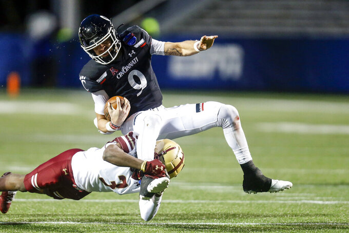 Cincinnati quarterback Desmond Ridder (9) is tackled by Boston College defensive back Jason Maitre (3) as he carries the ball during the first half of the Birmingham Bowl NCAA college football game Thursday, Jan. 2, 2020, in Birmingham, Ala. (AP Photo/Butch Dill)