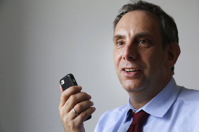 FILE - In this Wednesday, March 25, 2015 file photo, StoryCorps founder Dave Isay holds a smartphone in the Brooklyn borough of New York. One Small Step, which Isay established in 2018, is among a growing number of nonprofit initiatives whose aim is to narrow America's increasingly toxic political divide. (AP Photo/Mark Lennihan)