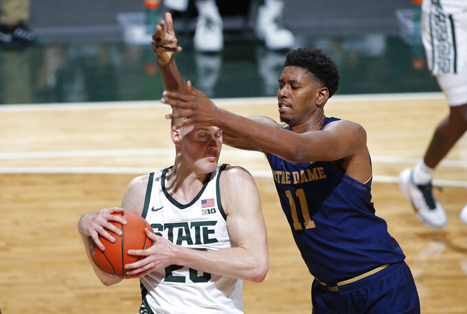 Michigan State's Joey Hauser, left, and Notre Dame's Juwan Durham vie for a rebound during the first half of an NCAA college basketball game, Saturday, Nov. 28, 2020, in East Lansing, Mich. (AP Photo/Al Goldis)