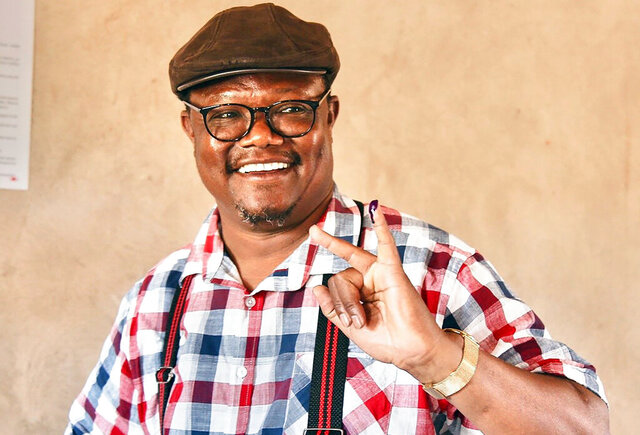 FILE - In this Wednesday Oct. 28, 2020 file photo, CHADEMA party presidential candidate Tundu Lissu smiles as he shows his finger marked with ink after casting his vote at Ntewa Primary School polling station in Ikungi town Singida region, Tanzania. Escorted by Western diplomats, Tanzania's main opposition candidate Tundu Lissu left the country for Belgium on Tuesday, Nov. 10, 2020 after rejecting a presidential election he asserted had